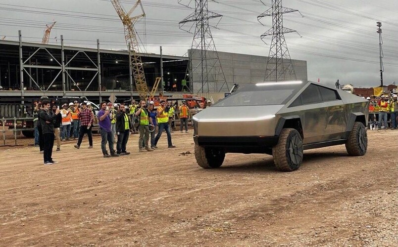 During a factory visit, a prototype of Cybertruck is next to the Texas Gigafactory under construction